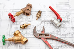 Plan plumber and wrench. Plumbing Tools Arranged On House Plans whit wrench and water valves Royalty Free Stock Photos
