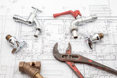 Plan plumber and wrench. Plumbing Tools Arranged On House Plans whit wrench and water valves Royalty Free Stock Photography
