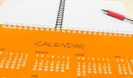 Plan por Año Nuevo, calendario anaranjado con la pluma y cuaderno en el escritorio de oficina Imagenes de archivo