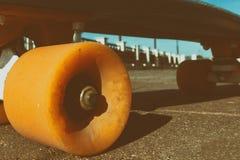 Plan rapproché à faire de la planche à roulettes roues sur la route rugueuse de brique 80& x27 ; tonalité artistique de style de  image stock