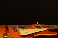 Plan rapproché électrique de guitare de bleus de corps solide sur le fond noir, avec l'abondance de l'espace de copie Foyer sélec Images stock
