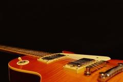 Plan rapproché électrique de guitare de roche de corps solide sur le fond noir, avec l'abondance de l'espace de copie Foyer sélec Photos stock