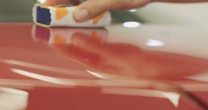 Plan rapproché appliquant le revêtement en céramique sur la voiture rouge photos libres de droits