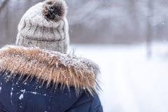 Plan rapproché arrière de vue de femme marchant dehors en chutes de neige fraîches photographie stock