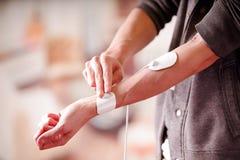 Plan rapproché avec des électrodes d'electrostimulator dans le bras d'un jeune homme de forme physique à un arrière-plan brouillé Photo libre de droits