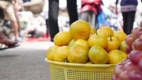 Plan rapproché beaucoup de mandarine et raisins oranges dans un panier au marché vietnamien local banque de vidéos