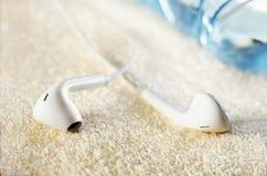 Plan rapproché blanc d'écouteurs et une bouteille de l'eau sur une serviette éponge Image stock