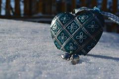 Plan rapproché bleu de coeur de vintage dans la neige dans le premier plan Photos libres de droits