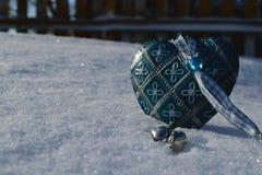 Plan rapproché bleu de coeur de vintage dans la neige dans le premier plan Photographie stock libre de droits