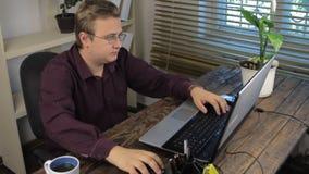 Plan rapproché, boisson d'une tasse, travaillant avec une souris d'ordinateur et un clavier d'ordinateur portable banque de vidéos