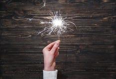 Plan rapproché brûlant de cierge magique de partie de nouvelle année dans la main femelle sur le fond noir Photographie stock libre de droits