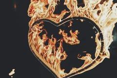 Plan rapproché brûlant de coeur avec des flammes, exposition étonnante du feu la nuit a Photos libres de droits