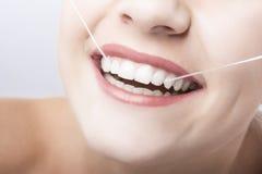 Plan rapproché caucasien de bouche de femme avec le fil dentaire. photographie stock libre de droits