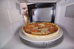 Plan rapproché classique de pizza dans la micro-onde Produit demi-complet placé en four pour chauffer image stock
