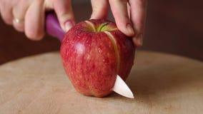 Plan rapproché coupant la pomme rouge sur un conseil en bois banque de vidéos