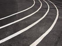 Plan rapproché courant de voie avec le blanc courbant des lignes peintes sur le noir Photographie stock libre de droits