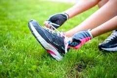 Plan rapproché d'active pulsant le coureur femelle, préparant des chaussures Photo libre de droits