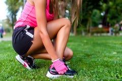 Plan rapproché d'active pulsant le coureur femelle, préparant des chaussures pour le TR Photo stock