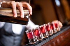 Plan rapproché d'alcool se renversant de main de barman Photos libres de droits