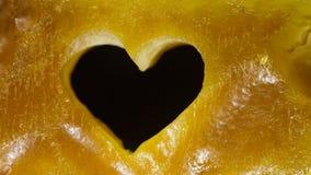 Plan rapproché d'ambre d'or avec le symbole d'amour de coeur comme fond Images libres de droits