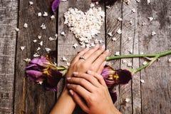 Plan rapproché d'anneau de proposition en main avec la forme de coeur du lilas blanc la Floride Photographie stock