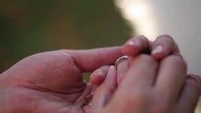 Plan rapproché d'anneaux de mariage macro mettant l'anneau sur vos bijoux de diamon d'or blanc de doigt banque de vidéos