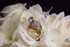 Plan rapproché d'anneaux de mariage sur la rose de blanc Photographie stock