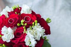 Plan rapproché d'anneaux de mariage sur le bouquet de fleur de la jeune mariée Photo libre de droits