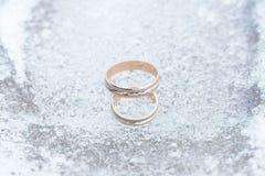 Plan rapproché d'anneaux de mariage sur le fond de glace Image stock