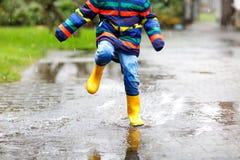 Plan rapproché d'enfant portant les bottes jaunes de pluie et marchant pendant le verglas, la pluie et la neige le jour froid image stock