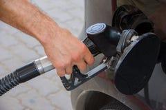 Plan rapproché d'essence de pompage d'essence de l'homme dans le véhicule à la station service Photo stock