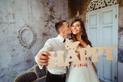 Plan rapproché d'heureux en bois de lettrage tenu en épousant des couples Photographie stock libre de droits