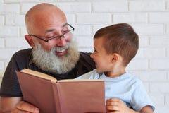 Plan rapproché d'homme âgé et de petit garçon avec un livre regardant chaque o Photo stock