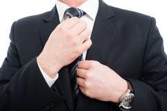 Plan rapproché d'homme élégant ajustant le sien costume de port de lien Photos libres de droits