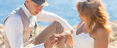 Plan rapproché d'homme bel mettant sur le doigt blond de sourire de jeunes mariées d'anneau à la plage Photos libres de droits
