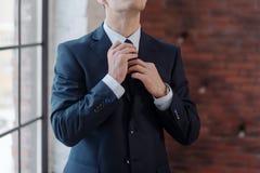 Plan rapproché d'homme d'affaires ajustant sa cravate se tenant dans le bureau images stock