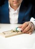 Plan rapproché d'homme d'affaires prenant l'attrait d'argent de la souricière à clapet Photo stock