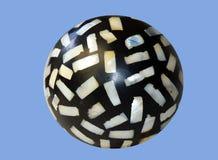 Plan rapproché d'isolement d'une pierre noire de spiracle avec les puces nacrées incorporées sur un fond bleu images stock