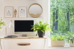 Plan rapproché d'un écran d'ordinateur moderne sur un bureau par la fenêtre dedans Image stock