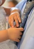 Plan rapproché d'un baby& x27 ; main de s sur un father& x27 ; lien de s Photos libres de droits