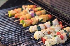 Plan rapproché d'un barbecue où des brochettes de poulet sont faites cuire Photos libres de droits