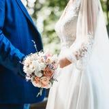 Plan rapproché d'un bouquet du ` s de jeune mariée dans les mains d'un couple affectueux Images stock