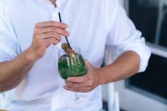 Plan rapproché d'un cadre cultivé d'un cocktail avec la menthe dans des mains masculines Un type dans une chemise blanche tient u images libres de droits
