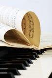 Plan rapproché d'un clavier de piano et des notes de la musique Photographie stock libre de droits