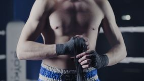 Plan rapproché d'un combattant mélangé d'arts martiaux enveloppant ses mains avant un combat Le boxeur enveloppe sa main un banda photo stock