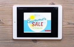Plan rapproché d'un comprimé numérique avec la bannière d'offre de vente sur un écran d'isolement sur le fond en bois photos stock