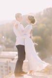 Plan rapproché d'un couple romantique de nouveaux mariés regardant l'un l'autre et l'embrassant avec leurs bras sur le fond de vi Image libre de droits