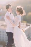 Plan rapproché d'un couple romantique de nouveaux mariés regardant l'un l'autre et l'embrassant avec leurs bras sur le fond de vi Images libres de droits