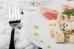 Plan rapproché d'un déjeuner de fantaisie Un plat avec une fourchette sur le blanc lapide le fond Prosciutto rouge, basilic vert  Image libre de droits