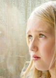 Plan rapproché d'un de l'adolescence regardant à l'extérieur un hublot Images libres de droits